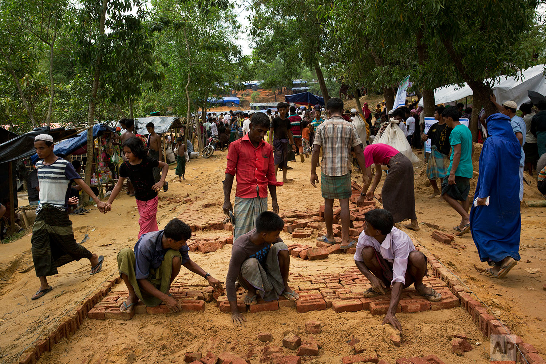 In this Saturday, Sept. 23, 2017 photo, people lay bricks to build a pavement at a new Rohingya settlement in Lambashia, near Kutupalong. (AP Photo/Bernat Armangue)