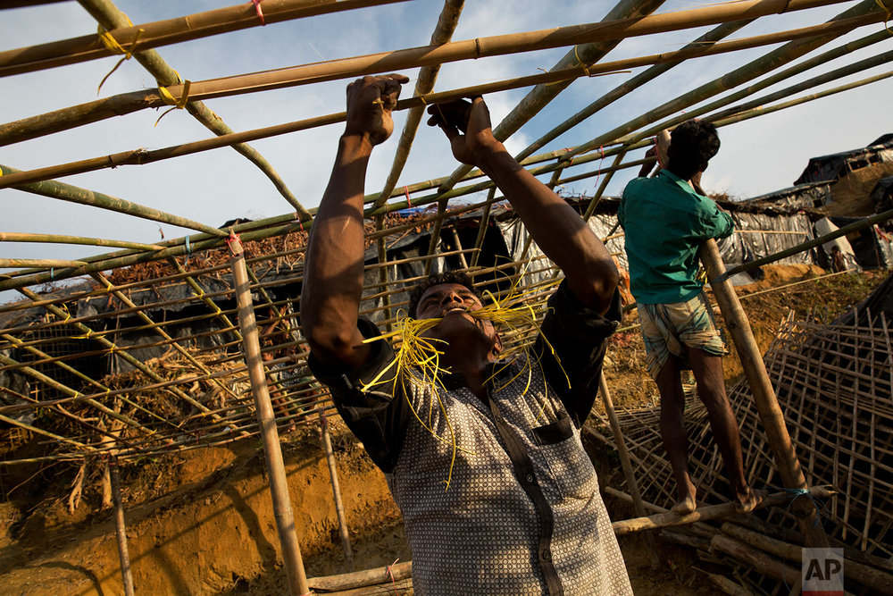In this Sept. 24, 2017 photo, Rohingya Muslims build new shelters in Balukhali refugee camp, Bangladesh. (AP Photo/Bernat Armangue)