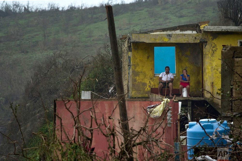 A couple sits in their home in El Negro, Puerto Rico on Thursday, Sept. 21, 2017, a day after the impact of Hurricane Maria. A day after Maria ravaged Puerto Rico, flooding towns, crushing homes and killing at least two people, millions of people on the island faced the dispiriting prospect of weeks and perhaps months without electricity. (AP Photo/Carlos Giusti)