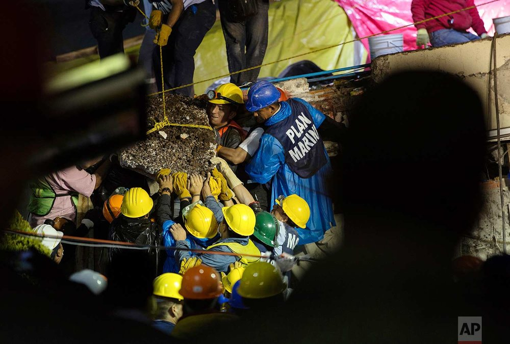 Search and rescue team members work to bring down a large piece of concrete during rescue efforts at the Enrique Rebsamen school in Mexico City, Mexico, Thursday, Sept. 21, 2017, in an effort to reach a young girl buried in the rubble of the school. (AP Photo/Anthony Vazquez)