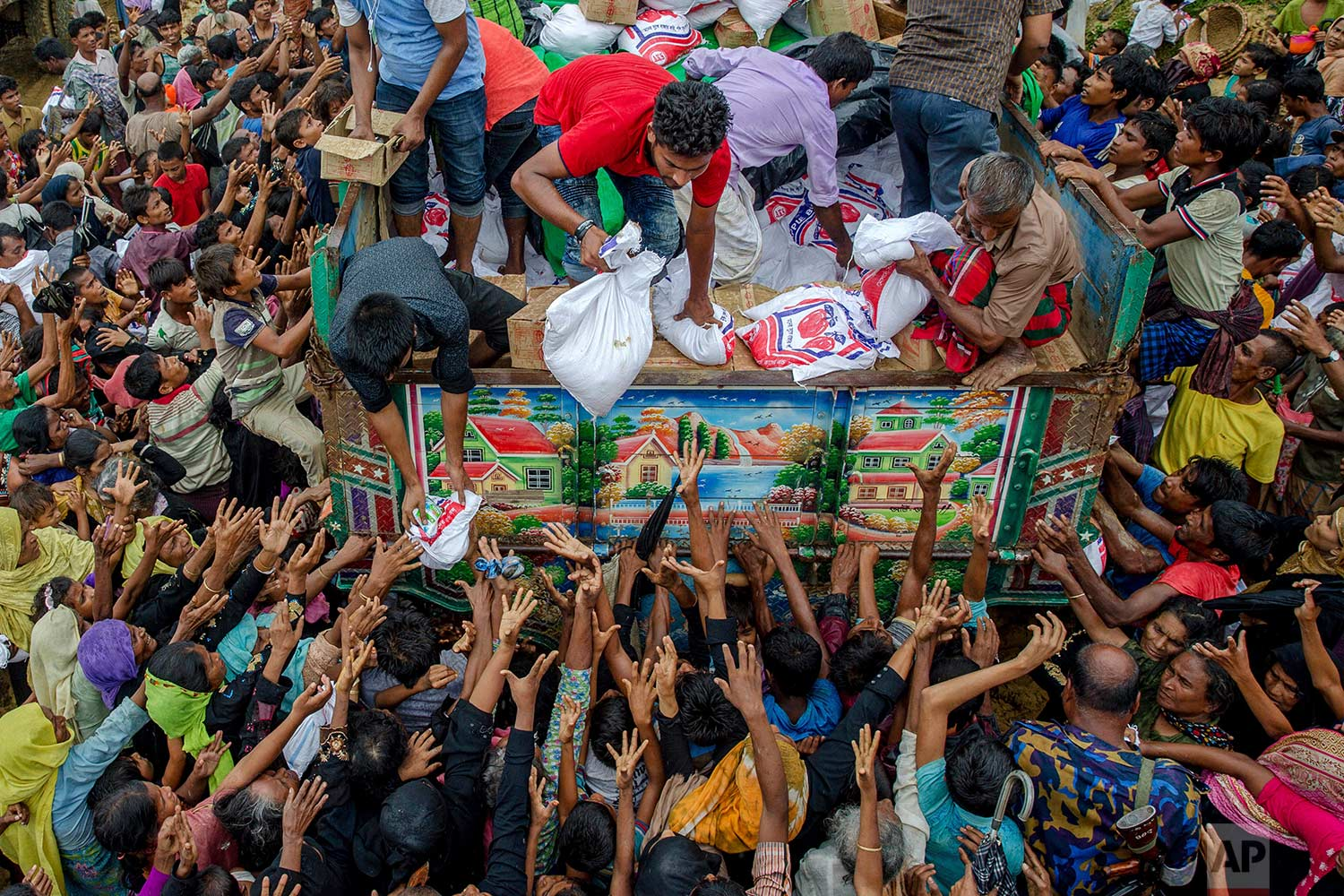 Rohingya Muslims, who travelled from Myanmar into Bangladesh, stretch their arms out to collect food items distributed by aid agencies near Balukhali refugee camp, Bangladesh, Monday, Sept. 18, 2017. (AP Photo/Dar Yasin)