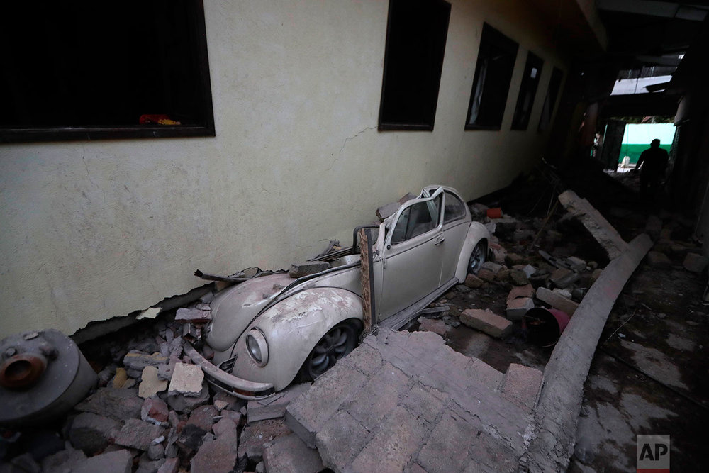 A car sits crushed from a building felled by a 7.1 earthquake, in Jojutla, Morelos state, Mexico, Wednesday, Sept. 20, 2017. (AP Photo/Eduardo Verdugo)