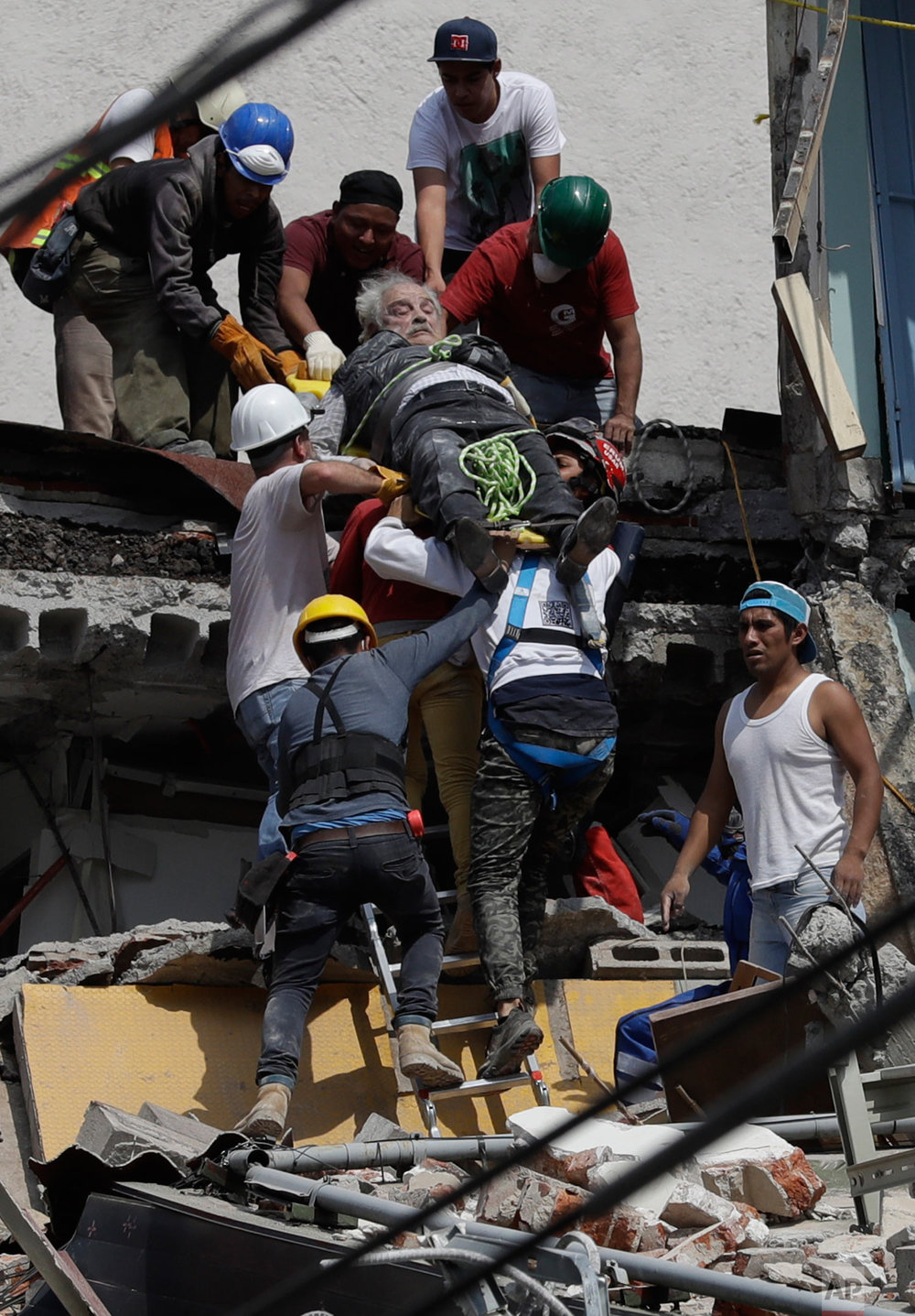 An injured man is pulled out of a building that collapsed during an earthquake in the Roma Norte neighborhood of Mexico City, Tuesday, Sept. 19, 2017. (AP Photo/Rebecca Blackwell)
