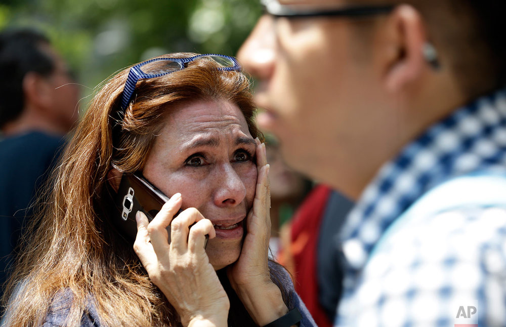 A woman tries to reach people on her cellphone after she evacuated with others to Paseo de la Reforma Avenue after an earthquake in Mexico City, Tuesday, Sept. 19, 2017. (AP Photo/Marco Ugarte)