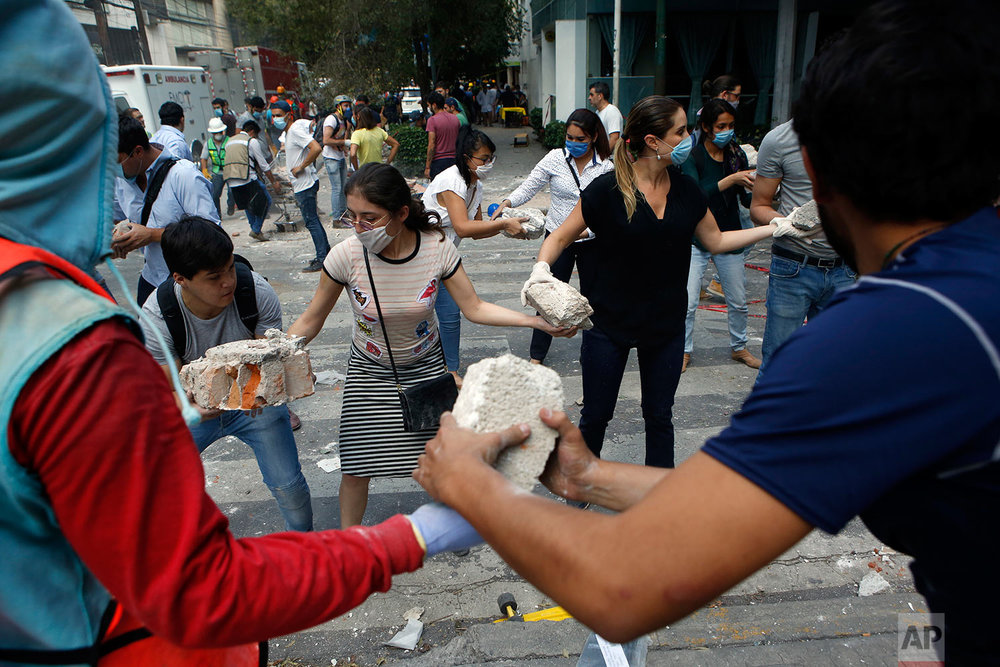 Volunteers pick up the rubble from a building that collapsed during an earthquake in the Condesa neighborhood of Mexico City, Tuesday, Sept. 19, 2017. (AP Photo/Rebecca Blackwell)