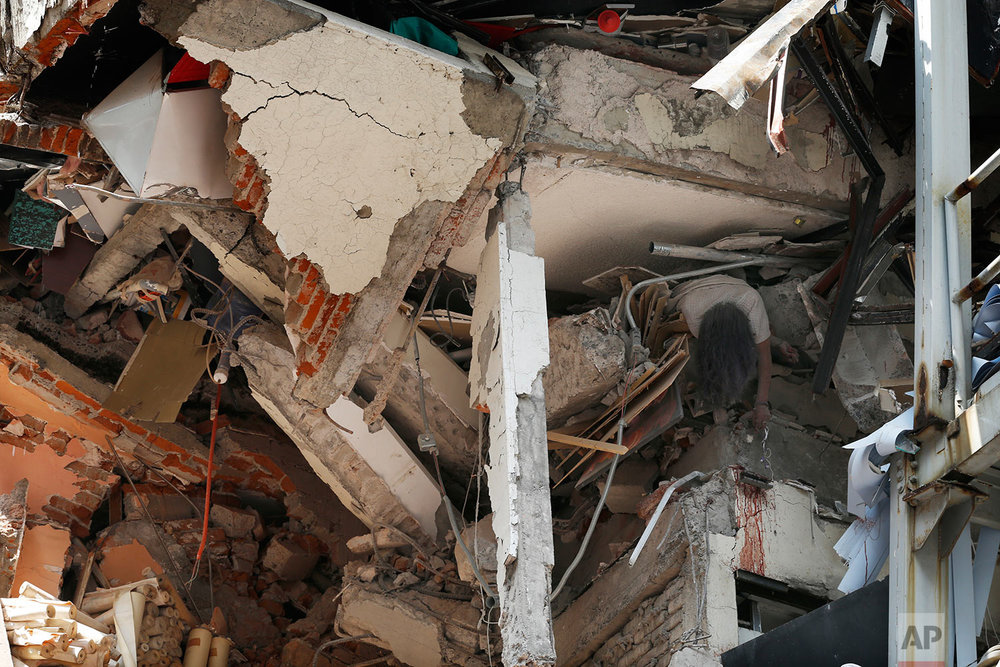 The body of woman hangs crushed by a collapsed building in the neighborhood of Roma Norte, in Mexico City, Tuesday, Sept. 19, 2017.  (AP Photo/Marco Ugarte)