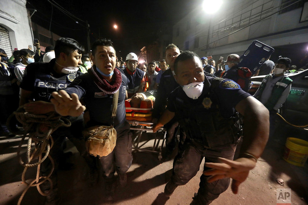 Emergency personnel rush past with a gurney carrying a victim rescued from the rubble of a building that collapsed during a 7.1 earthquake, in the Colonia Obrera neighborhood of Mexico City, Tuesday, Sept. 19, 2017. (AP Photo/Miguel Tovar)