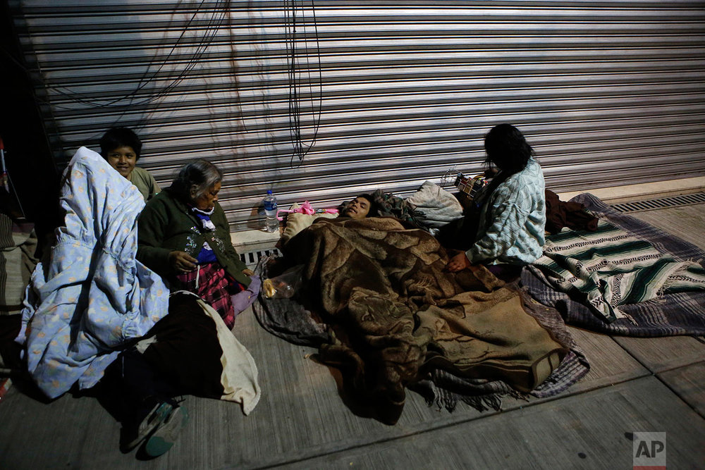 Families fearing aftershocks sleep on the street in the Roma neighborhood of Mexico City, Tuesday, Sept. 19, 2017. (AP Photo/Rebecca Blackwell)