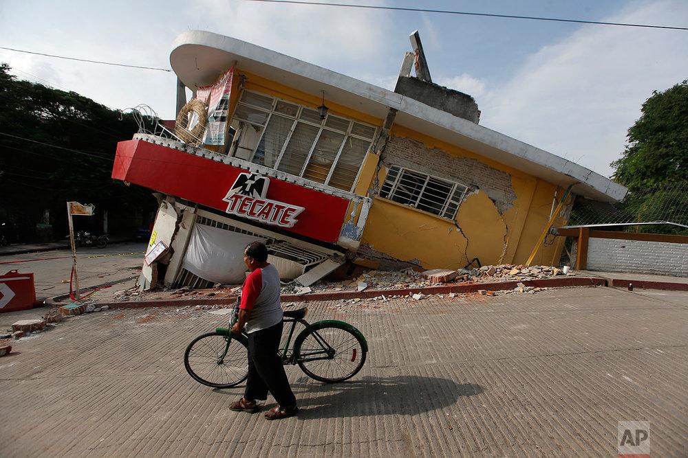 A man walks his bike past a building felled by a 7.1 earthquake, in Jojutla, Morelos state, Mexico, Wednesday, Sept. 20, 2017.  (AP Photo/Eduardo Verdugo)