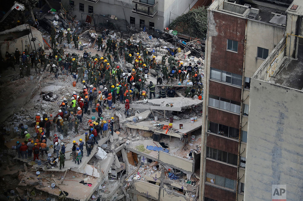 Rescue workers search for people trapped inside a collapsed building felled by a 7.1 magnitude earthquake in the Del Valle area of Mexico City, Wednesday, Sept. 20, 2017. (AP Photo/Rebecca Blackwell)