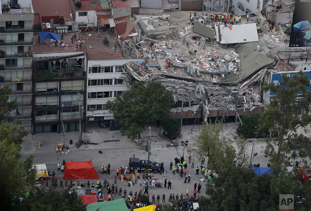 Rescue workers search for people trapped inside a collapsed building in the Roma Norte neighborhood of Mexico City, Wednesday, Sept. 20, 2017. (AP Photo/Rebecca Blackwell)