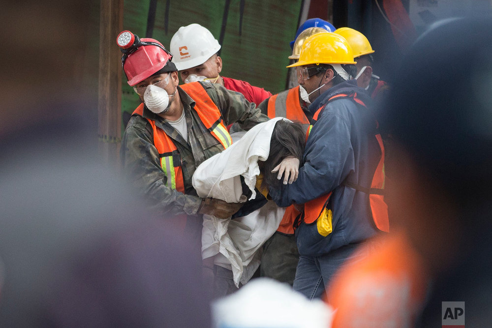 Rescue workers carry a body recovered from a building felled by a 7.1 magnitude earthquake, in the Ciudad Jardin neighborhood of Mexico City, Thursday, Sept. 21, 2017. (AP Photo/Moises Castillo)