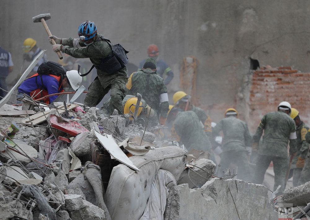 Rescue workers search for survivors at an apartment building located on the street corner of Amsterdam and Laredo, that collapsed during an earthquake in the Condesa neighborhood of Mexico City, Thursday, Sept. 21, 2017. (AP Photo/Natacha Pisarenko)