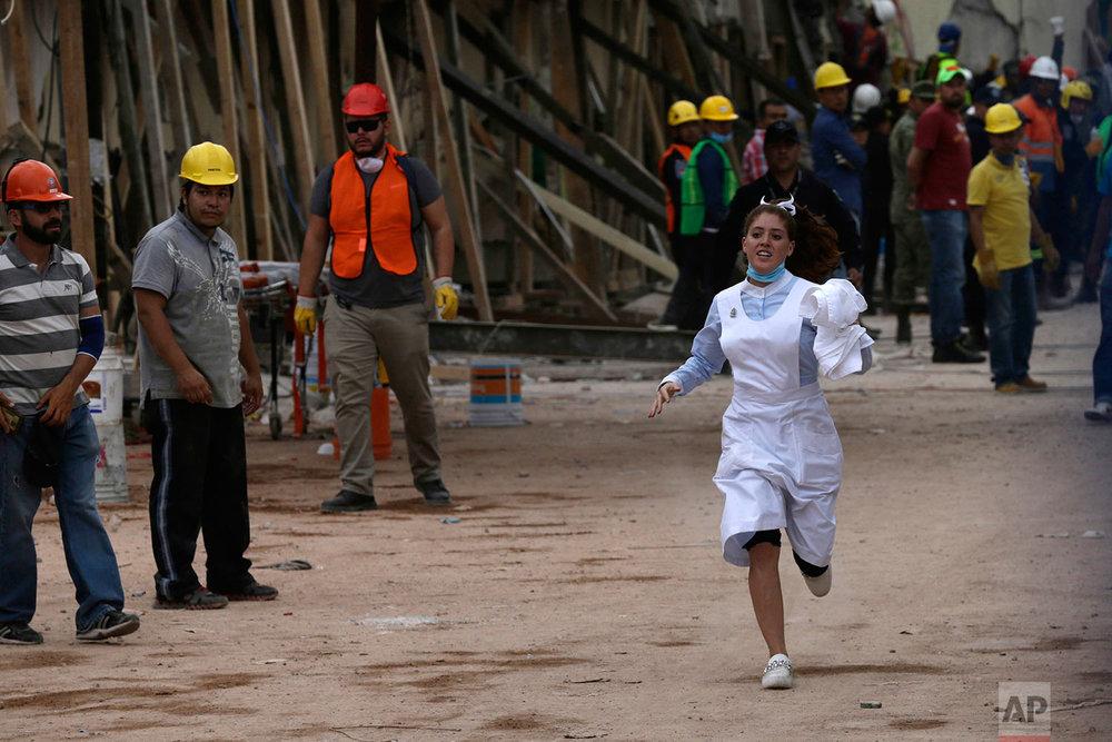 A nurse runs during rescue efforts at the Enrique Rebsamen school in Mexico City, Mexico, Wednesday, Sept. 20, 2017.  (AP Photo/Marco Ugarte)