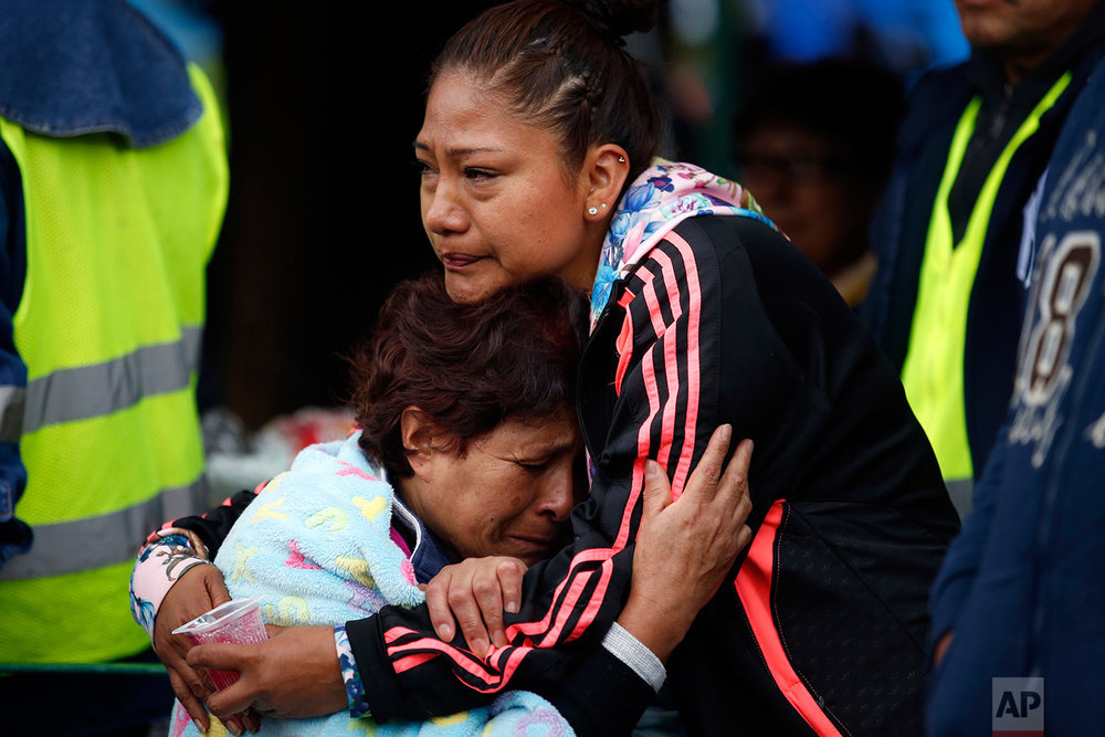 Family members embrace as they wait for news of their relatives outside a quake-collapsed seven-story building in Mexico City's Roma Norte neighborhood, Friday, Sept. 22, 2017. (AP Photo/Rebecca Blackwell)