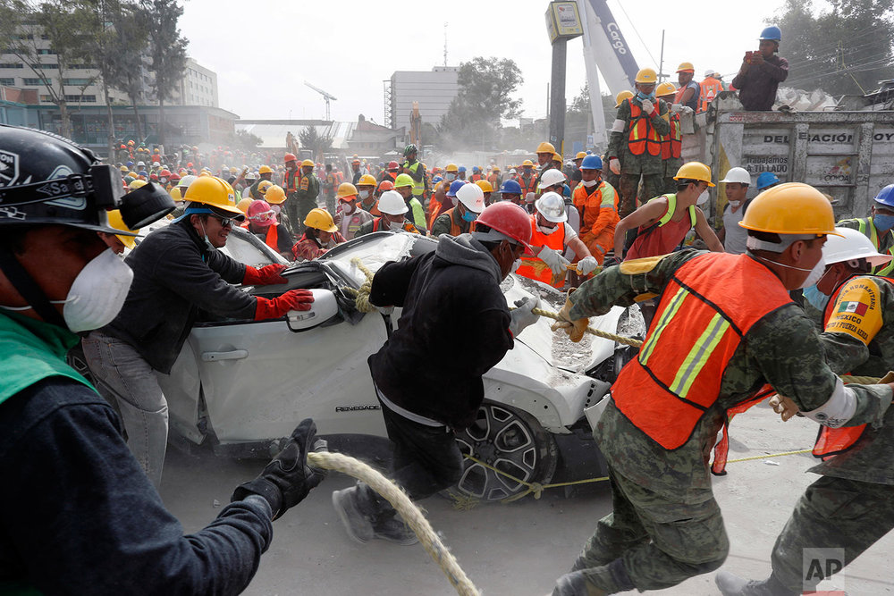 Volunteers and soldiers remove a destroyed vehicle from a parking lot of a four-story clothing factory felled by a 7.1 magnitude earthquake, in Mexico City, Friday, Sept. 22, 2017. (AP Photo/Dario Lopez-Mills)