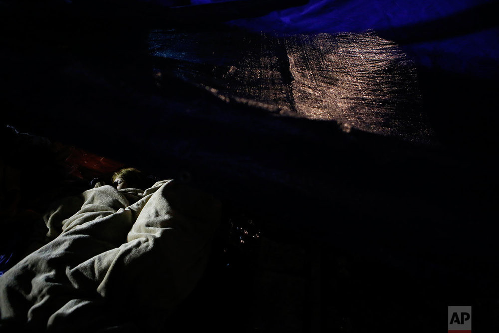 Family members who have been camped out for days nap under a tarp alongside the collapsed office building where they believe their relatives are trapped, in the Roma Norte neighborhood of Mexico City, just after midnight on Sept. 23, 2017, more than three days after a 7.1 magnitude earthquake toppled buildings. (AP Photo/Rebecca Blackwell)