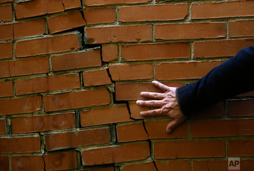 Architect Victor Marquez checks a cracked wall that was not caused by the recent earthquake during his survey of a seven-floor apartment building, in Mexico City's Roma neighborhood, Friday, Sept. 22, 2017. (AP Photo/Marco Ugarte)