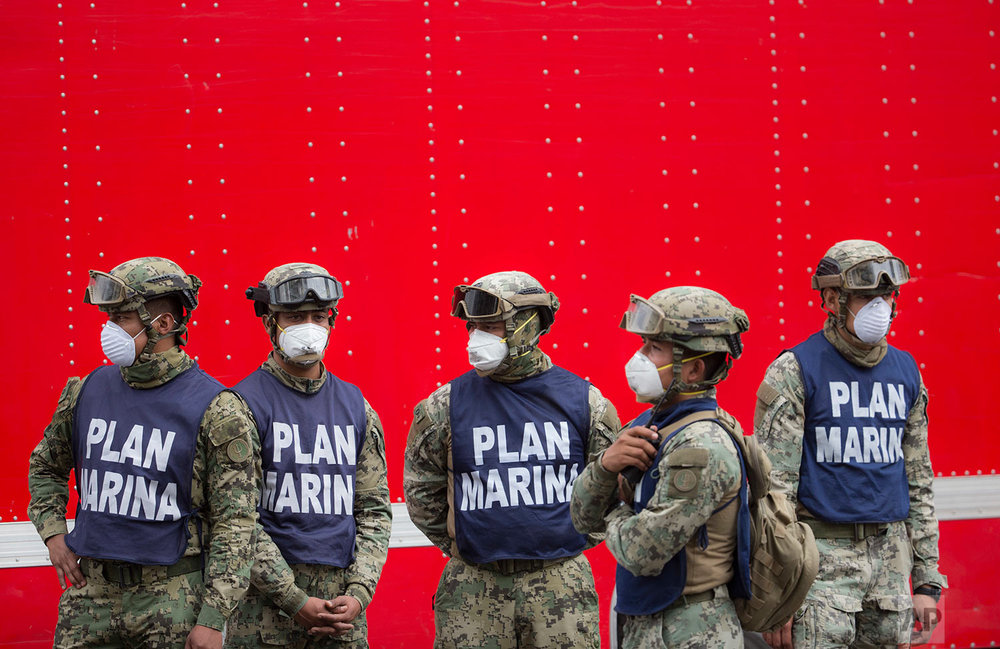 Mexican Marine soldiers stand guard at a search and rescue site of a felled office building brought down by a 7.1-magnitude earthquake, in the Roma Norte neighborhood, in Mexico City, Saturday, Sept. 23, 2017. (AP Photo/Moises Castillo)