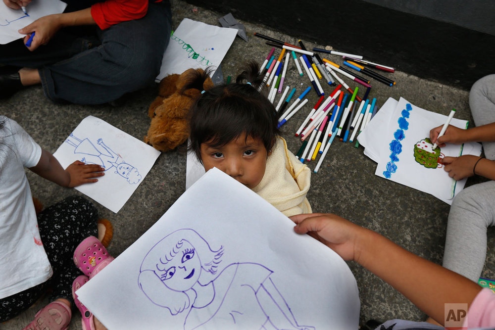 Children from an Otomi indigenous family pass the time drawing, on the sidewalk of their apartment building after it was declared uninhabitable by authorities after Tuesday's 7.1 earthquake, at the corner of Guanajuato and Monterrey streets in the Roma neighborhood of Mexico City, Saturday, Sept. 23, 2017. (AP Photo/Marco Ugarte)