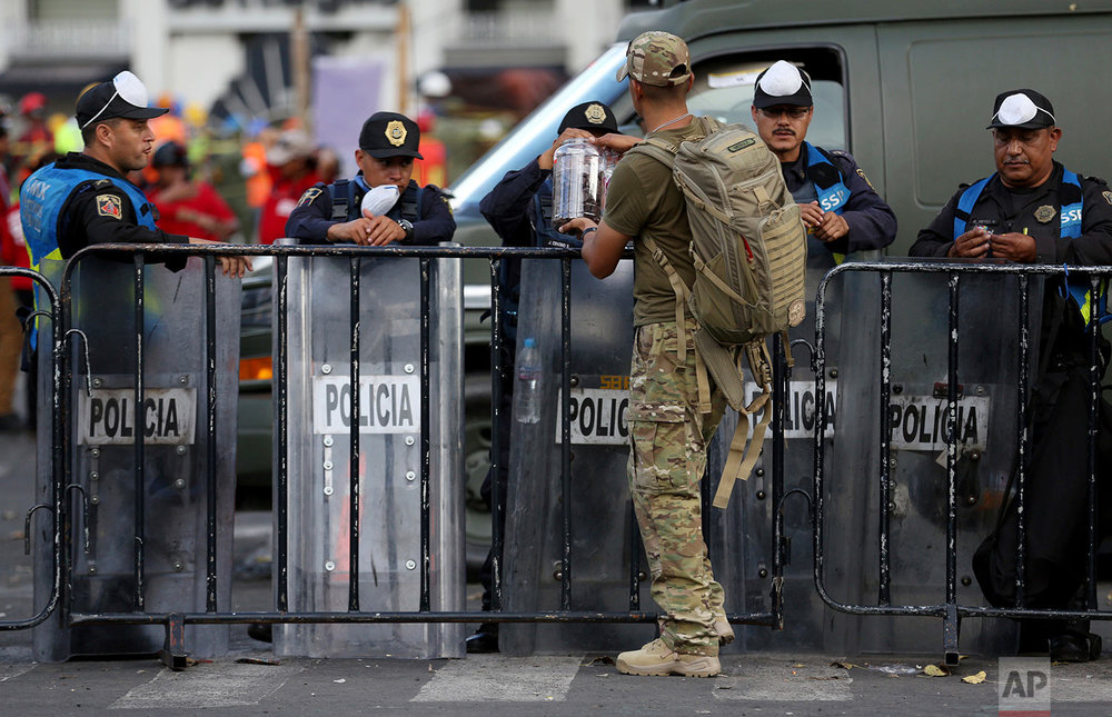 In this Sept. 22, 2017 photo, a civilian dressed in fatigues passes out chocolate to police guarding the site of an office building that collapsed during Tuesday's 7.1 earthquake, as search and rescue operations continue there at the corner of Oaxaca and Alvaro Obregon streets in the Roma Norte neighborhood in Mexico City. (AP Photo/Gustavo Martinez Contreras)