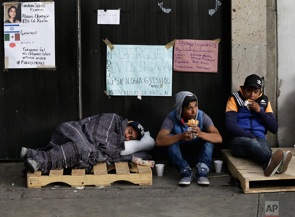 Volunteers take a break from rescue efforts on the outskirts of an office building that was felled by a 7.1-magnitude earthquake during their search for survivors, in the Roma Norte neighborhood of Mexico City, Sunday, Sept. 24, 2017. (AP Photo/Marco Ugarte)