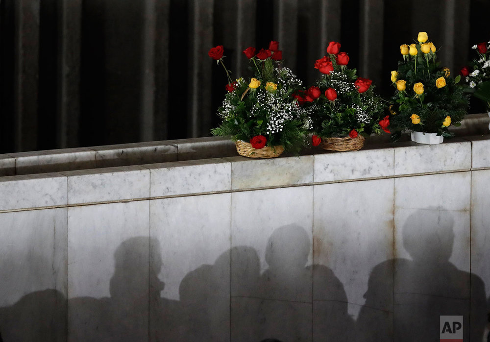 The shadows of Catholic faithful are cast on a wall where people have placed flower offerings, during a Mass remembering the victims of the recent 7.1-magnitude earthquake, at the Basilica of Guadalupe, in Mexico City, Sunday, Sept. 24, 2017. (AP Photo/Rebecca Blackwell)