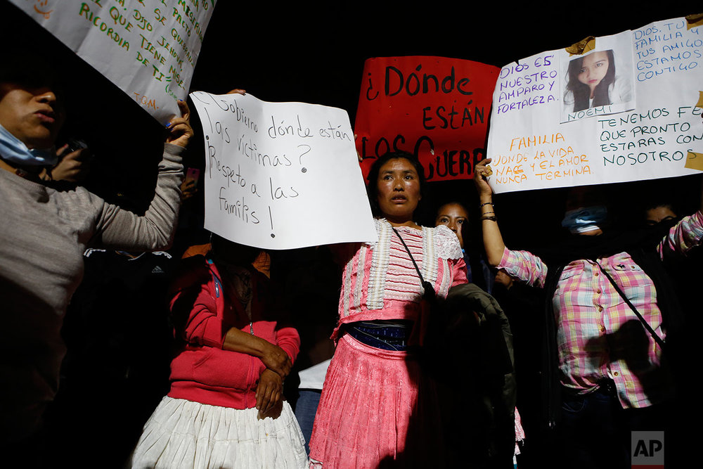 """Family members frustrated over a lack of information and results at a rescue operation in the Roma Norte neighborhood hold up signs reading """"Where are the bodies?"""" and showing pictures of missing relatives, as they protest in Mexico City, Sunday, Sept. 24, 2017. (AP Photo/Rebecca Blackwell)"""