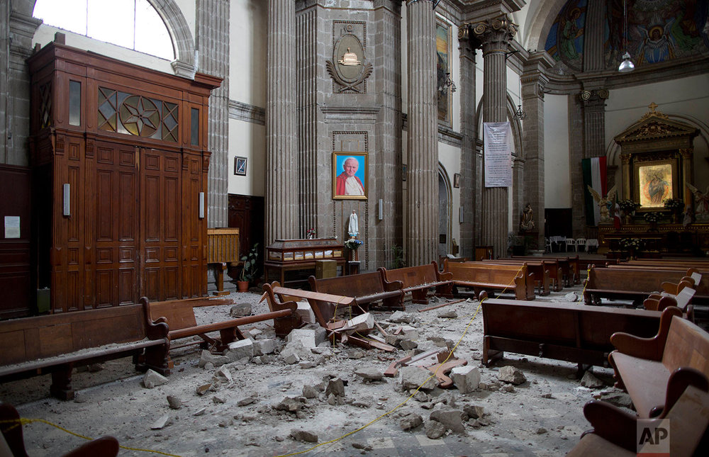 Debris from the cupola of the Our Lady of Angels Church is scattered on the wooden pews and floor below a framed image of Pope John Paul II, in Mexico City, Sunday, Sept. 24, 2017. (AP Photo/Enric Marti)
