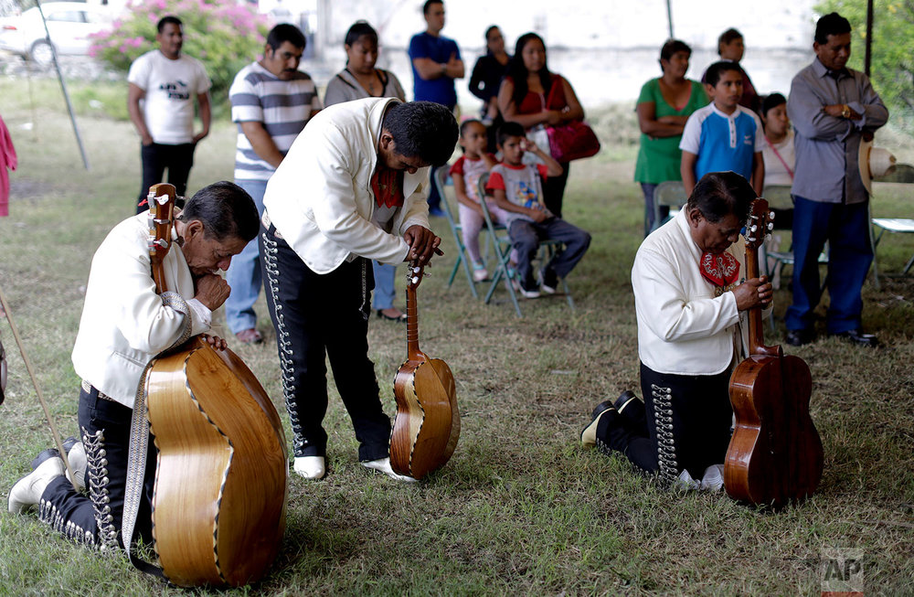 In this Saturday, Sept. 23, 2017 photo, mariachis pray during a wedding ceremony in an empty lot in front of a church that was collapsed by the recent earthquake, in Atzala, Mexico. As the church shifted to recovery mode, the planned church wedding instead took place outside. (AP Photo/Natacha Pisarenko)