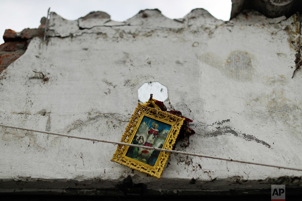 In this Saturday, Sept. 23, 2017 photo, a framed image of a religious icon hangs precariously on a cracked wall of the Santiago Apostol church destroyed during the recent 7.1-magnitude earthquake, in Atzala, Mexico. Little remains of the golden yellow church with a red roof where a child's baptism turned into tragedy when the roof of a church collapsed as the powerful earthquake shook central Mexico. Eleven members of a family died, including the 2-month-old girl being christened. (AP Photo/Natacha Pisarenko)