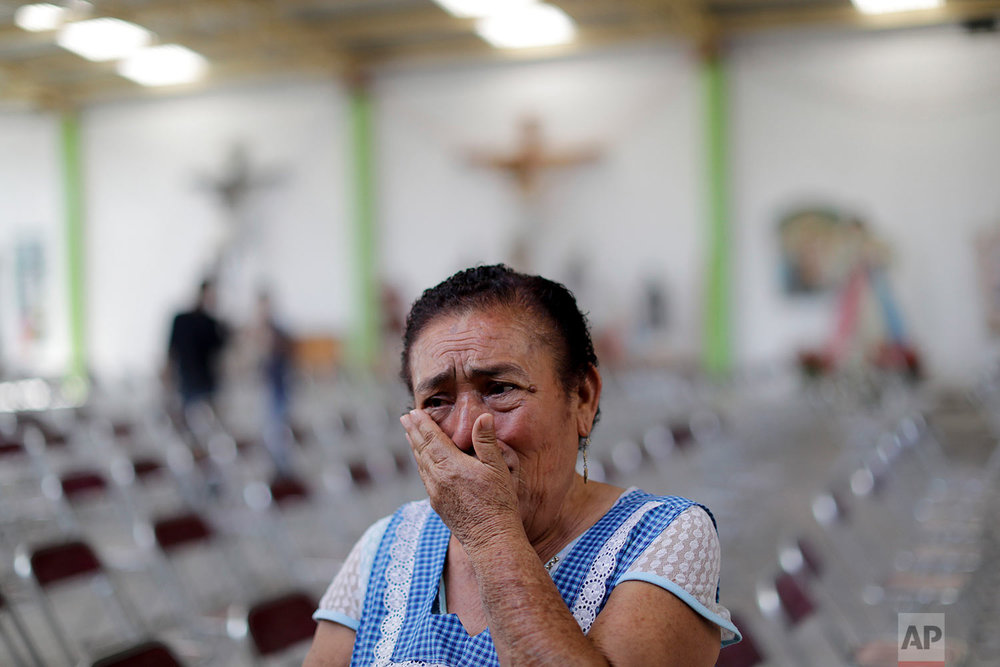 Teresa Cantu Luna, 66, cries as she stands before a collection of religious statues that had to be removed from a quake-damaged church for their safe keeping, in Tepeojuma, Mexico, Sunday, Sept. 24, 2017. The Archdiocese of Mexico says more than 150 religious temples in this deeply Catholic country were damaged during the deadly quake. Many of the battered buildings are in the state of Puebla, where the epicenter was located. (AP Photo/Natacha Pisarenko)