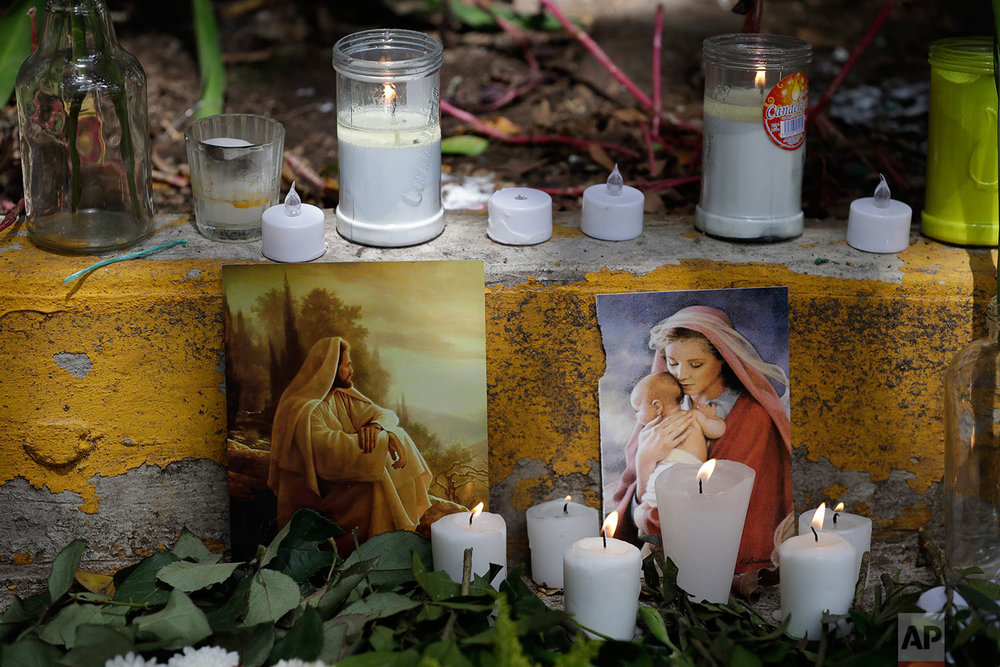 Candles surround Catholic images in a street altar erected near the site of a toppled building in Amsterdam Street in the Condesa neighborhood of Mexico City, Sunday, Sept. 24, 2017. As rescue operations stretched into day 6, residents throughout the capital have held out hope that dozens still missing might be found alive.(AP Photo/Rebecca Blackwell)