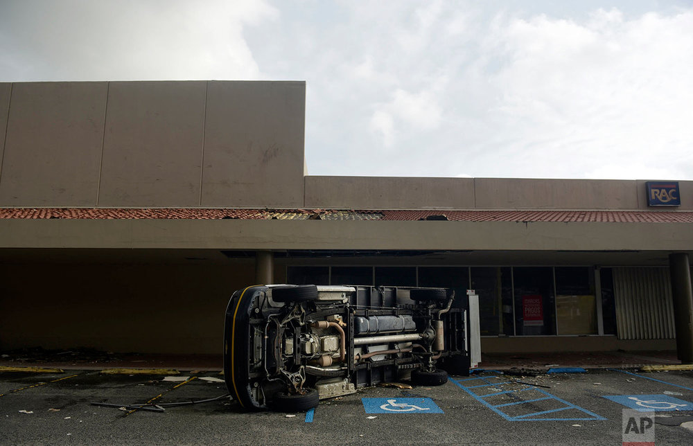 An overturned vehicle stands in a parking lot after the passing of Hurricane Maria, in Yabucoa, Puerto Rico, Thursday, September 21, 2017. (AP Photo/Carlos Giusti)