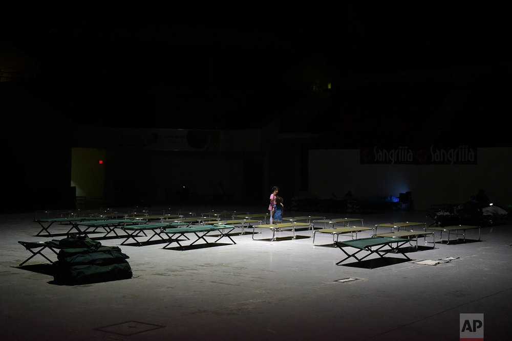 Two girls play on cots at Humacao Arena refugee center while waiting for the imminent impact of Maria, a Category 5 hurricane that threatens to hit the eastern region of the island with sustained winds of 175 miles per hour, in Humacao, Puerto Rico, Tuesday, September 19, 2017.  (AP Photo/Carlos Giusti)