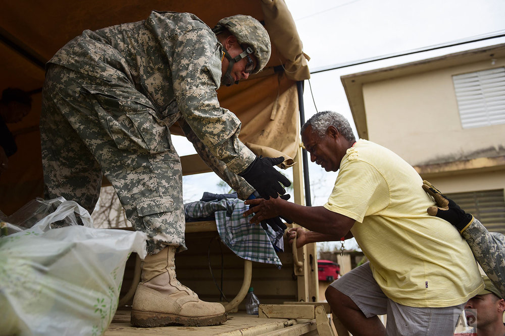 National Guard personnel evacuate Toa Ville resident Luis Alberto Martinez after the passing of Hurricane Maria, in Toa Baja, Puerto Rico, Friday, September 22, 2017. (AP Photo/Carlos Giusti)