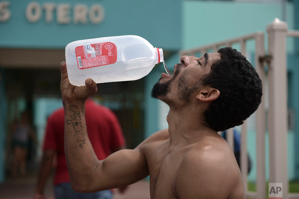 Julio Ortiz Montanez drinks water at the Jose Robles Otero Elementary School after the passing of Hurricane Maria, in Toa Baja, Puerto Rico, Friday, September 22, 2017. (AP Photo/Carlos Giusti)