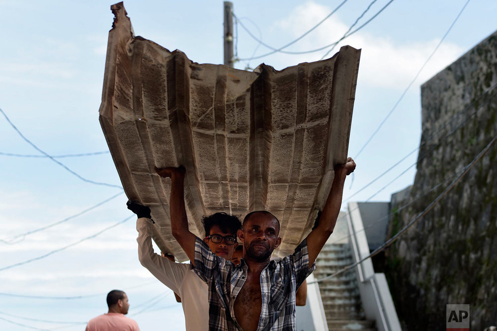 Residents from La Perla carry a piece of metal through the streets after Hurricane Maria, in San Juan, Puerto Rico, Monday, Sept. 25, 2017. The island territory of more than 3 million U.S. citizens is reeling in the devastating wake of Hurricane Maria. (AP Photo/Carlos Giusti)