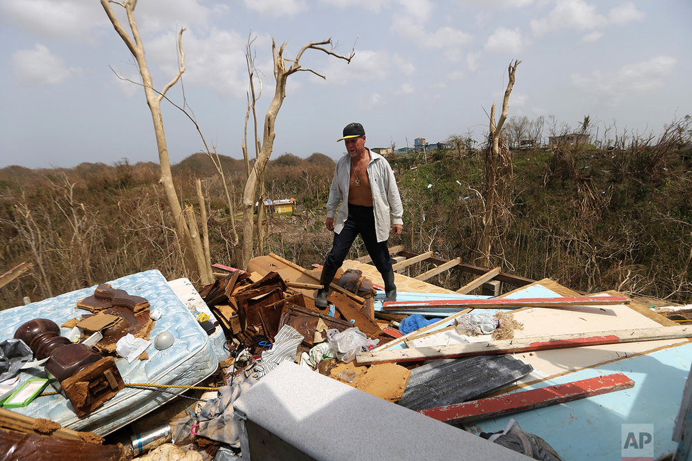 Jose Trinidad walks on what's left of his home in Montebello, Puerto Rico in the aftermath of Hurricane Maria, Tuesday, Sept. 26, 2017. (AP Photo/Gerald Herbert)