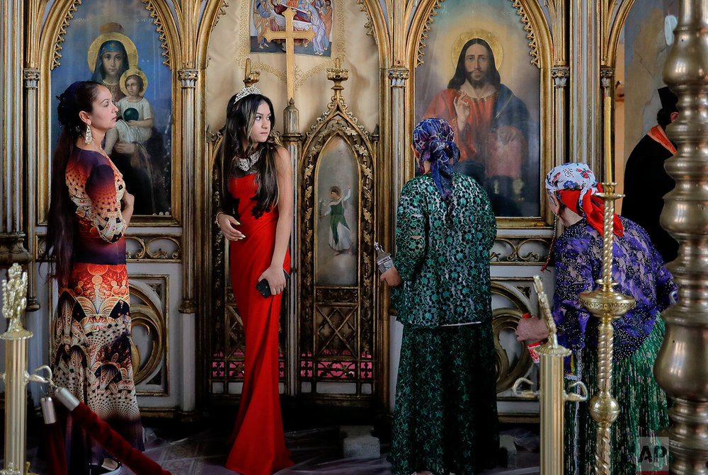 In this Friday, Sept. 8, 2017 photograph Roma women walk by the altar of the church in the Bistrita monastery compound touching the icons in Costesti, Romania. (AP Photo/Vadim Ghirda)