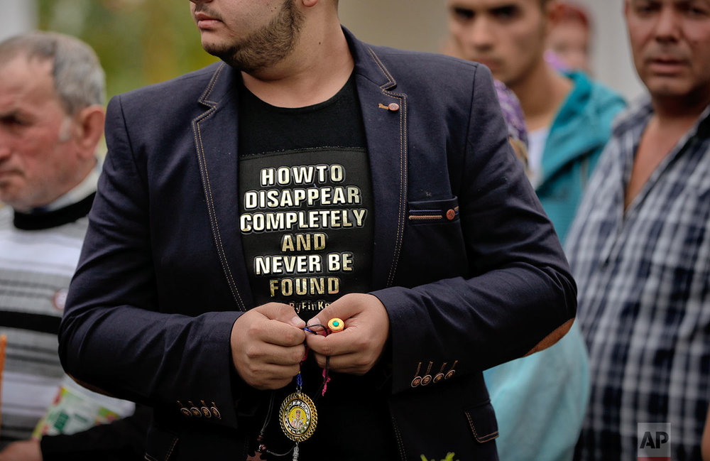 In this Friday, Sept. 8, 2017, photograph, a Roma man holds prayer beads as he waits in line to touch the holy remains of a saint at the Bistrita monastery compound in Costesti, Romania. (AP Photo/Vadim Ghirda)
