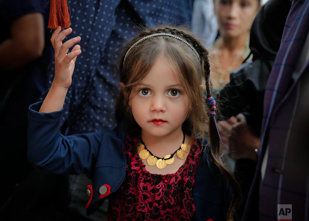 In this Friday, Sept. 8, 2017, photograph, a Roma girl reaches for decorations as she waits in line to touch holy remains at the Bistrita monastery in Costesti, Romania. (AP Photo/Vadim Ghirda)