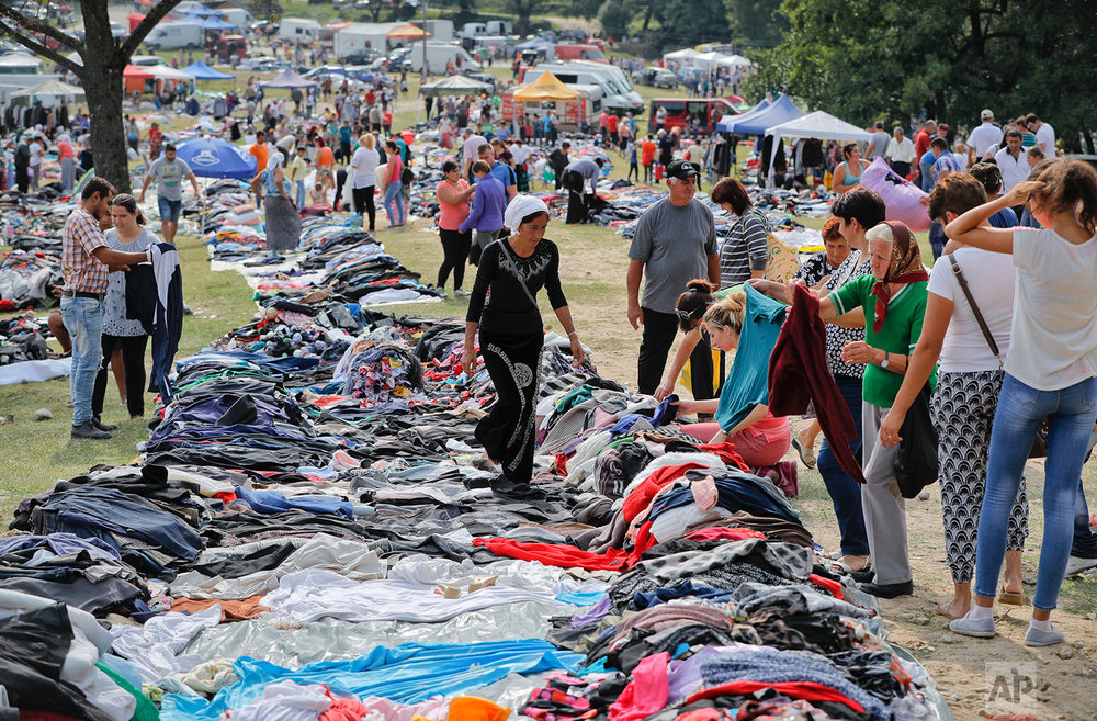 In this Friday, Sept. 8, 2017 photograph, a Roma woman vendor walks between piles of second hand clothing in Costesti, Romania. (AP Photo/Vadim Ghirda)