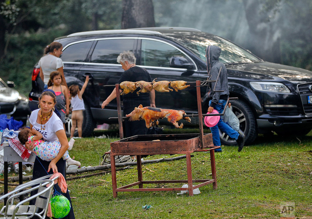 In this Friday, Sept. 8, 2017 photograph, piglets and chicken are roasting in Costesti, Romania. (AP Photo/Vadim Ghirda)