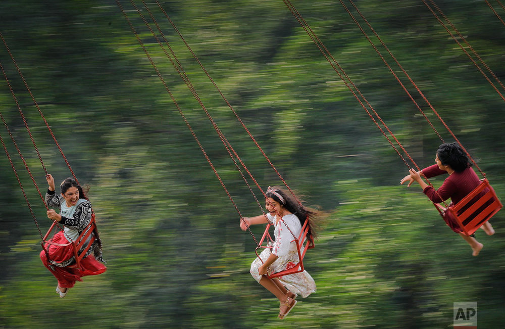In this Friday, Sept. 8, 2017 photograph, Roma girls enjoy a merry go round ride in Costesti, Romania. (AP Photo/Vadim Ghirda)
