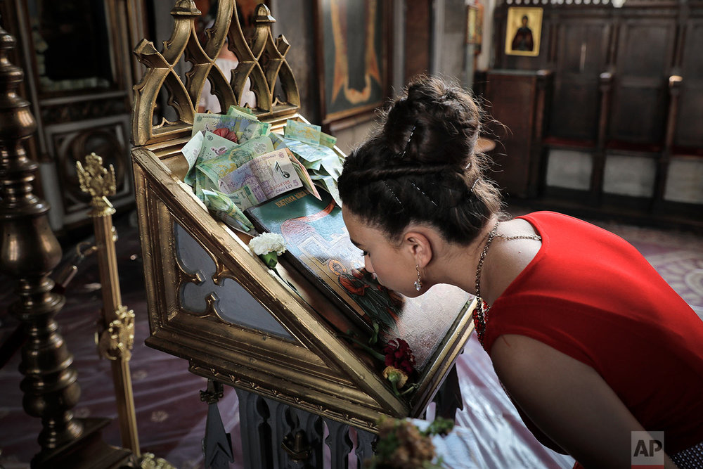 Roma girl kisses an icon with money placed around it at the church in the Bistrita monastery compound in Costesti, Romania during their annual celebration of the birthday of St. Mary, the mother of Jesus. (AP Photo/Vadim Ghirda)