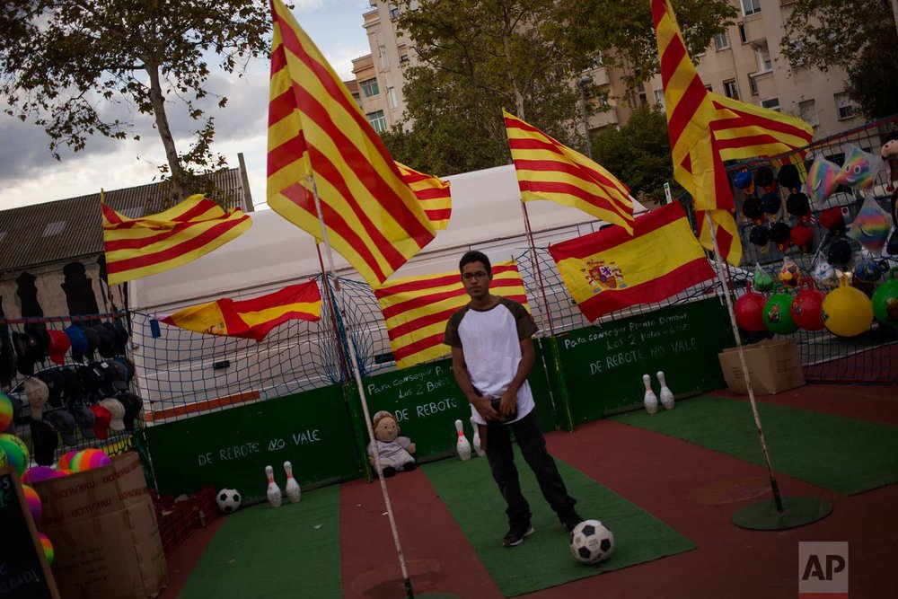 In this photo taken on Sunday, Sept. 17, 2017, a youth waits for customers to kick a soccer ball at some skittles in a street fair decorated with Catalan and Spanish flags in Barcelona, Spain, Sunday, Sept. 17, 2017. (AP Photo/Emilio Morenatti)