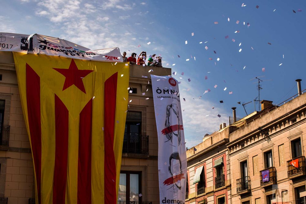 In this photo taken on Sept. 24, 2017, demonstrators throw ballot papers to the people gathering in Sant Jaume square in Barcelona, Spain. (AP Photo/Emilio Morenatti)