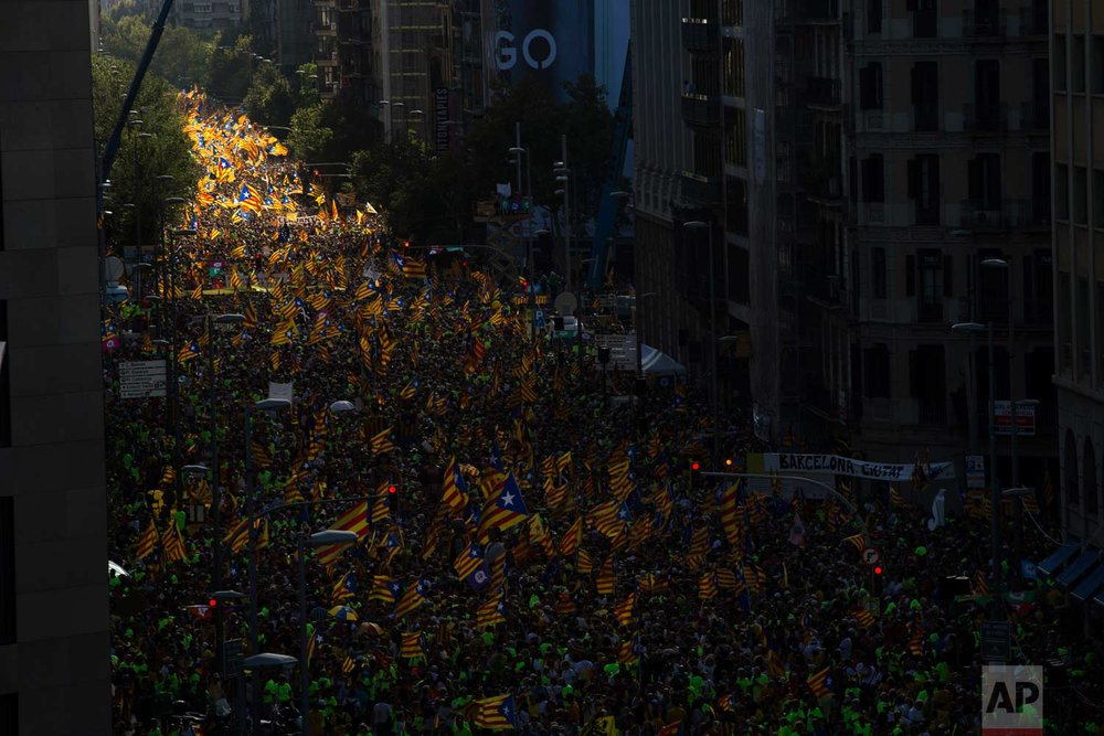"""In this photo taken on Monday Sept. 11, 2017, people wave """"estelada"""" or independence flags, during the Catalan National Day in Barcelona, Spain, Monday Sept. 11, 2017. (AP Photo/Emilio Morenatti)"""