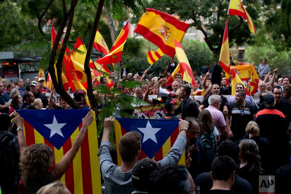 "In this photo taken on Friday, Sept. 22, 2017, pro-independence demonstrators hold ""esteladas"" or independence flags as right wing demonstrators wave Spanish flags, at the background, during a protest in Barcelona, Spain Friday, Sept. 22, 2017. (AP Photo/Emilio Morenatti)"